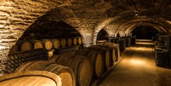 Old cellar with bottles and barrels under castle making wine