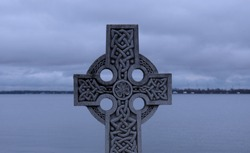 Old Celtic Cross stock images. Lake with celtic cross in the foreground stock images. Decorated celtic cross at dusk. Celtic cross in winter landscape