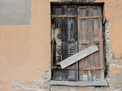 Old cement wall with nailed locked old wooden door. Pale brick colour wall with dead shut wooden door in old town Vilnius Lithuania with copy space for runaround or wraparound text