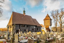 Old cemetery and wooden Church of St. John the Baptist with Renaissance bell tower built in 16th century in Slavonov village, Czech republic. Popular monument visited by tourists.Rural architecture