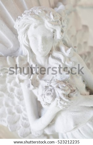 Old cemetery sculpture of the young girl, young angel holding flowers, peacefully and serenity concept