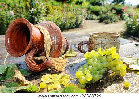 Old ceramic jug, mug and fresh grape on the wooden table