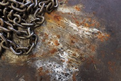 old chain on rusted metal sheet with soft-focus and over light in the background