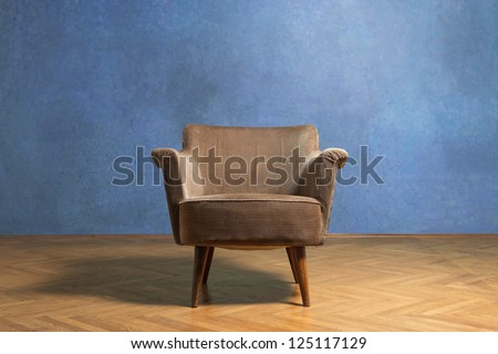 Old chair in grunge room with blue wall