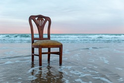Old chair on the ocean coast, dramatic sky, melancholic scene, loneliness