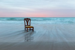 Old chair on the ocean coast, dramatic sky, melancholic scene, loneliness, long exposure