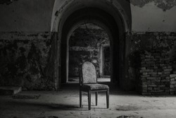 Old chair with backrest in dark, abandoned, spooky gallery, hall, castle, room in Daugavgriva fortress, Latvia