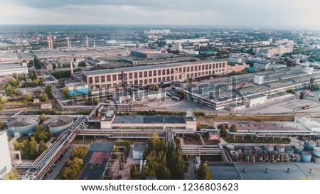 Old chemical factory with oil storage tank, pipes and refinery workshop, aerial view