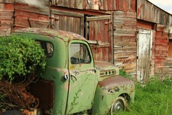 Old Chevy truck in front of old red barn