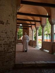 Old christian minister priest in white alb tunic Basilica di Santa Maria Assunta church Torcello cathedral Venice Italy