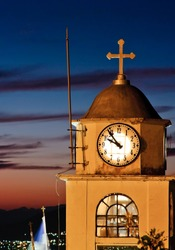 Old church clock against sunset in Greece