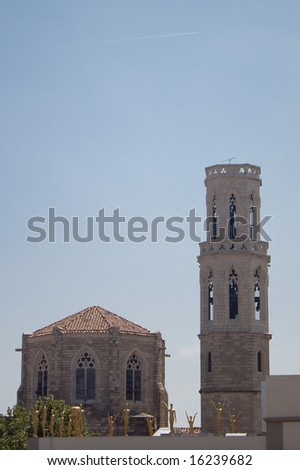 Old church in Figueras. Roof of Dali museum with golden statues on foreground