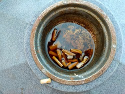 Old cigarettes filtered in the ashtray  water