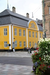 Old City Town Hall. Beautiful historic yellow and white painted building in the city center, Aalborg, Denmark.