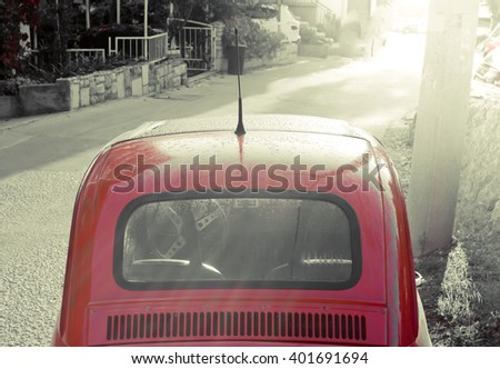 Old classic car with sun rays in background, summer morning in narrow city street. / Summer morning. / Toned photography.