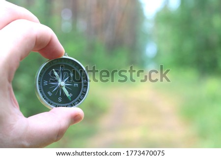 Old classic navigation compass in hand on natural background as symbol of tourism with compass, travel with compass and outdoor activities with compass