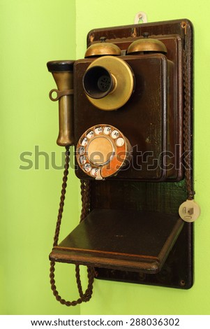 old classic wood telephone hanging on green wall