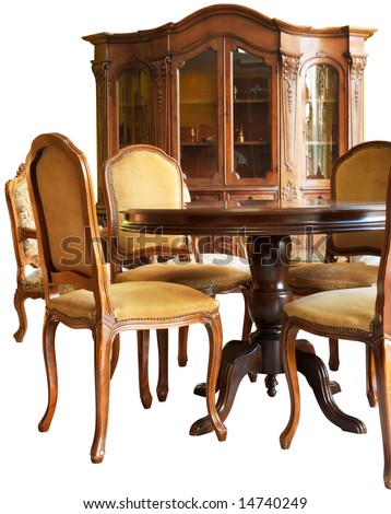 Old classic wooden furniture - a bookshelf, a table and chairs, all with handmade woodcarvings, isolated