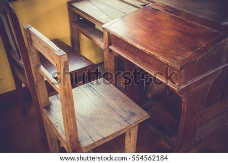Old classroom with wood desk and chair on dark floor with light from windows. #554562184