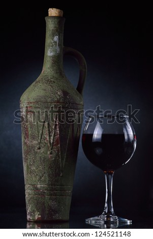 Old clay bottle of wine and glass.