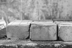Old clay bricks stacked together on a wood shelf, outdoors, at a location in South Louisiana. Horizontal black and white image.
