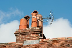 Old clay chimney pots and brick chimney stack on old tiled roof complete with TV aerial .