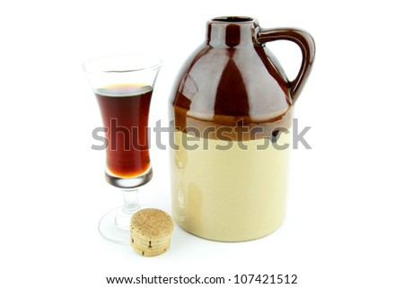 Old clay jug with a cork used to hold booze, with a filled glass next to it.