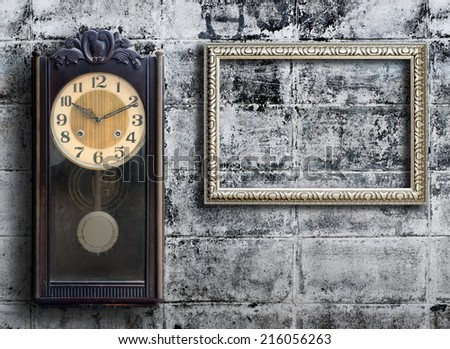 Old clock and empty picture frame on grunge wall.