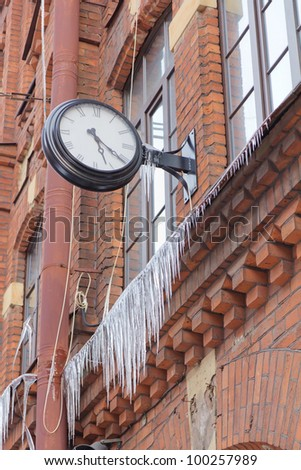 Old clock  and Long Icicles Hanging from Roof down to Red Brick Wall