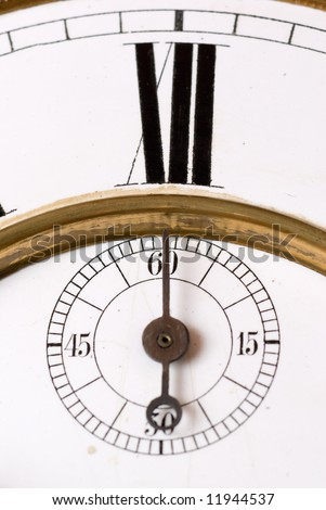 Old clock face detail with roman numerals - focus on the second hand.