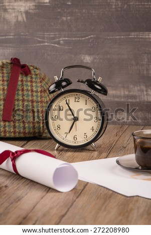 Old clock, hat coffee and paper sheets on old Wooden table.