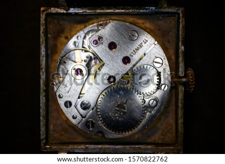 Old clock mechanism close-up on a black background. Vintage mechanical watch. Macro image.