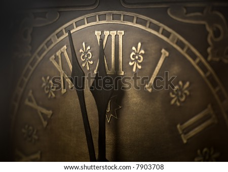Old clock with roman numerals. Selective focus on  number XII and minute hand. Intentional vignetting.