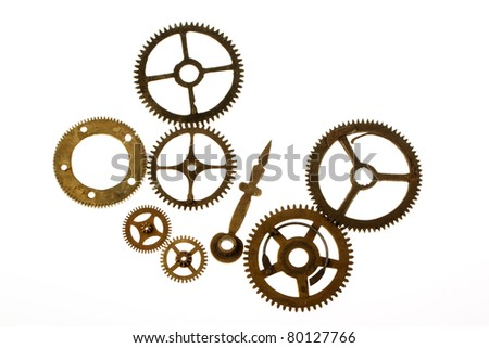 Old clockwork mechanism with brass metal cogs on white background
