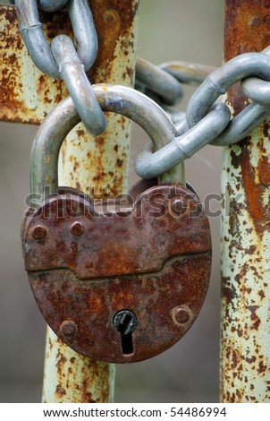 Old closed padlock on the rusty iron gate