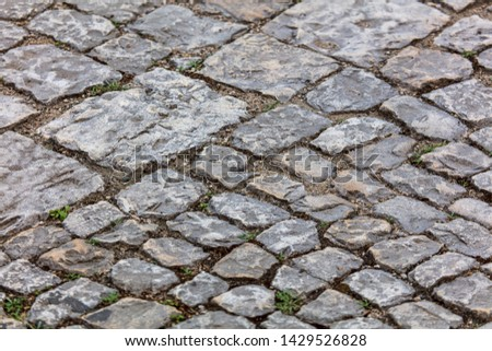 Old cobbles on the road as abstract background .
