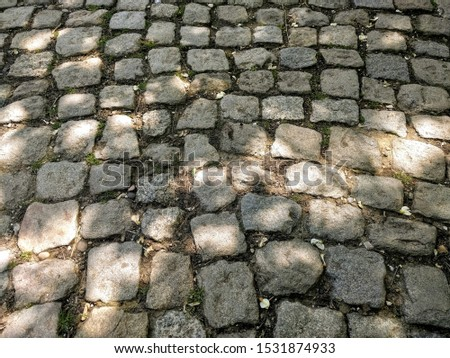 Old cobblestone path illuminated by the sun.