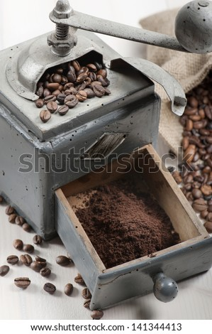 old coffee grinder with burlap and coffee beans on wooden table