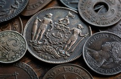 Old coins of different countries on a wooden table. Concept on history, numismatics, collecting, etc. Macro shot of ancient coins, money background. Shallow depth of field.