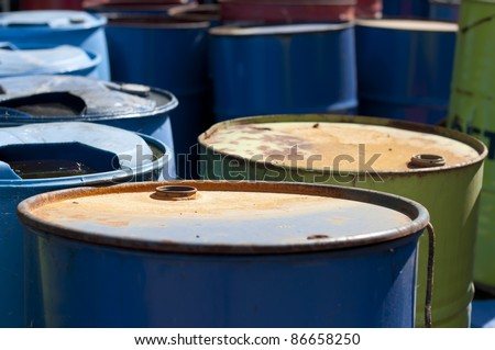 Old colored barrels for oil products. Empty rusted drums