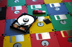 Old Colored Floppy disk with modern Hard Disk, Memory Pen USB and SD Memory Card. background