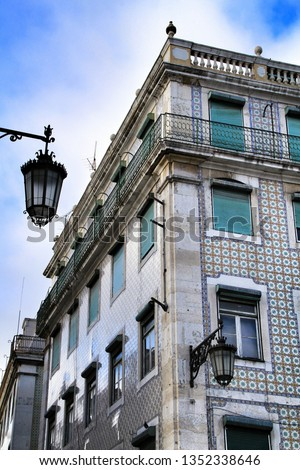 Old colorful and beautiful facades with vintage streetlight in Lisbon streets in Spring. Clothesline in the facade with hanging clothes #1352338646