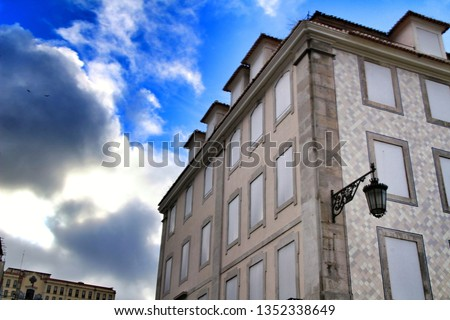 Old colorful and beautiful facades with vintage streetlight in Lisbon streets in Spring. Clothesline in the facade with hanging clothes #1352338649