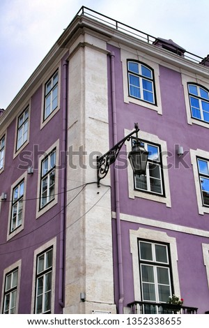 Old colorful and beautiful facades with vintage streetlight in Lisbon streets in Spring. Clothesline in the facade with hanging clothes #1352338655