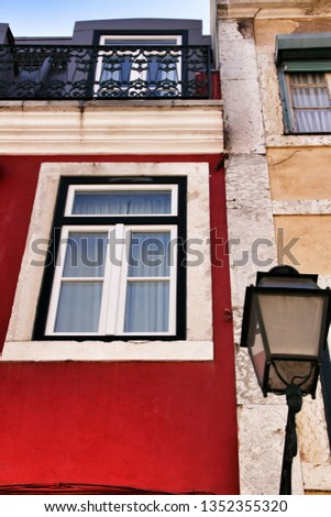 Old colorful and beautiful facades with vintage streetlight in Lisbon streets in Spring. Clothesline in the facade with hanging clothes #1352355320