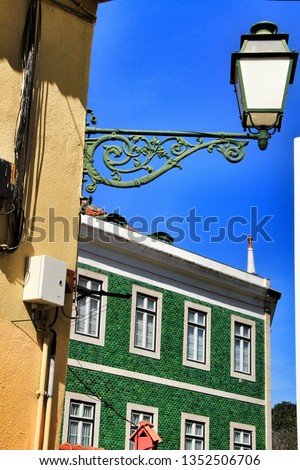 Old colorful and beautiful facades with vintage streetlight in Lisbon streets in Spring. Clothesline in the facade with hanging clothes #1352506706