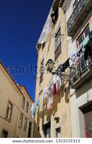 Old colorful and beautiful facades with vintage streetlight in Lisbon streets in Spring. Clothesline in the facade with hanging clothes #1353559313