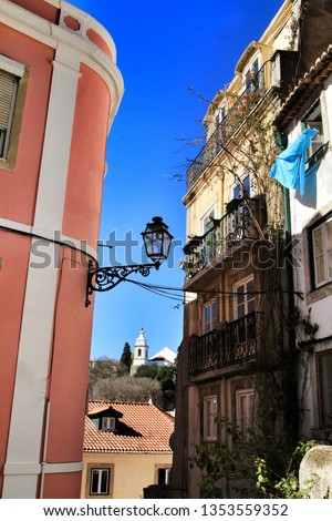 Old colorful and beautiful facades with vintage streetlight in Lisbon streets in Spring. Clothesline in the facade with hanging clothes #1353559352