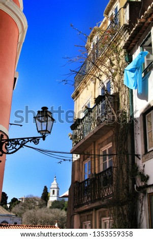 Old colorful and beautiful facades with vintage streetlight in Lisbon streets in Spring. Clothesline in the facade with hanging clothes #1353559358
