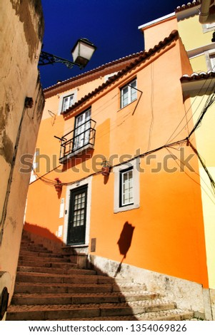 Old colorful and beautiful facades with vintage streetlight in Lisbon streets in Spring. Clothesline in the facade with hanging clothes #1354069826
